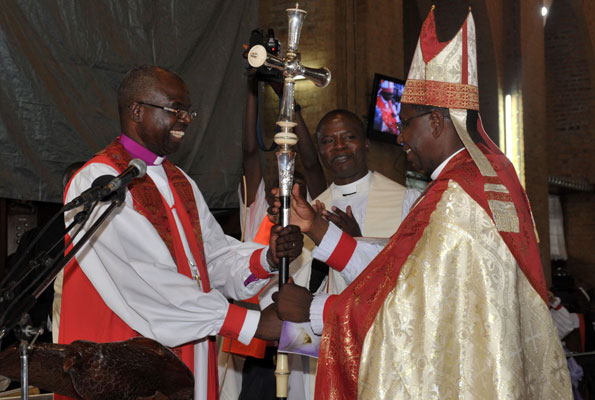 Outgoing Archbishop Henry Orombi (left) greets new Archbishop Stanley Ntagali. (Photo courtesy of the Monitor)