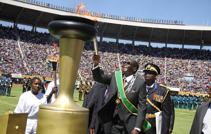 Zimbabwe President Robert Mugabe lights symbolic independence flame during the country's 33rd Independence Day celebration at National Sports Stadium. (Photo courtesy of Zimbabwe Herald)