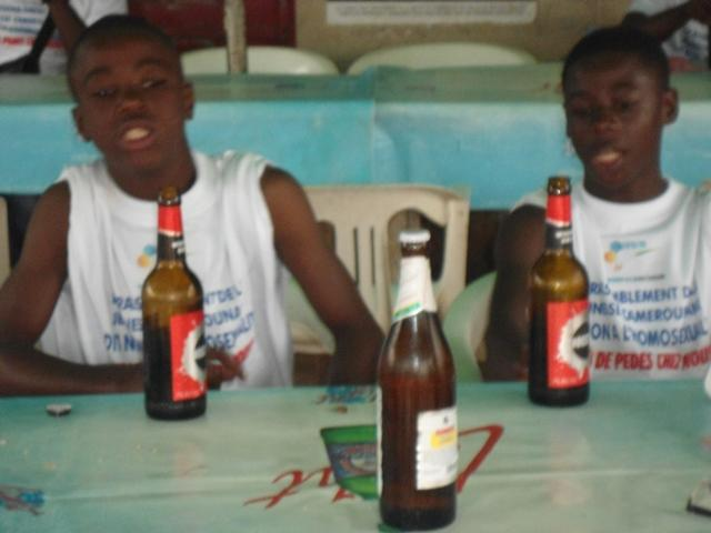 Boys in the anti-gay march in Yaounde refreshed themselves with beer.