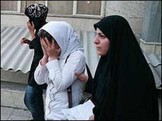 "Female member of basij militia (right) arrests a woman for revealing her hair (""bad hijab"") in 2013. (Photo courtesy of Paper Bird)"
