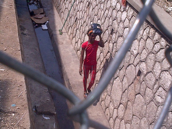 Youth walks through Shoemaker Gully before it was sealed shut after a raid on Dec. 23, 2014. (Photo courtesy of LoopJamaica.com)