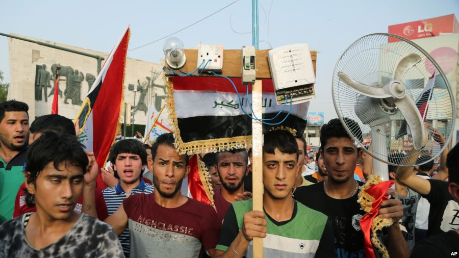 Protesters carry national flags and an electric fan in Baghdad in August 2015. (Photo courtesy of VOA)
