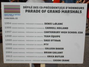 Parade sign at Ottawa Pride lists Denis LeBlanc as the grand marshal.