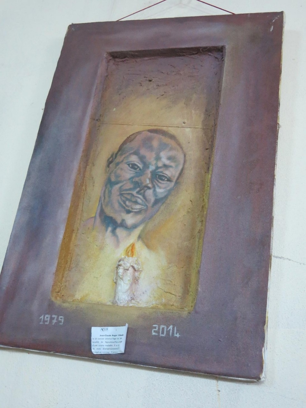 A painting in memory of Roger Mbede hangs in the office of a Cameroonian LGBT organization. (Robbie Corey-Boulet photo courtesy of Al Jazeera)