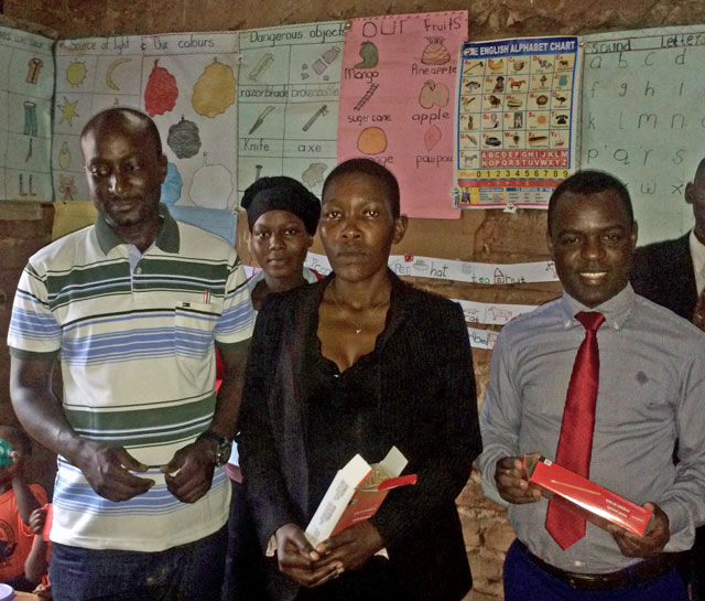 Frank Mugisha (right) with teachers at a Nsangi – Wakiso District school that received school supplies donated by Sexual Minorities Uganda. (Photo courtesy of SMUG)