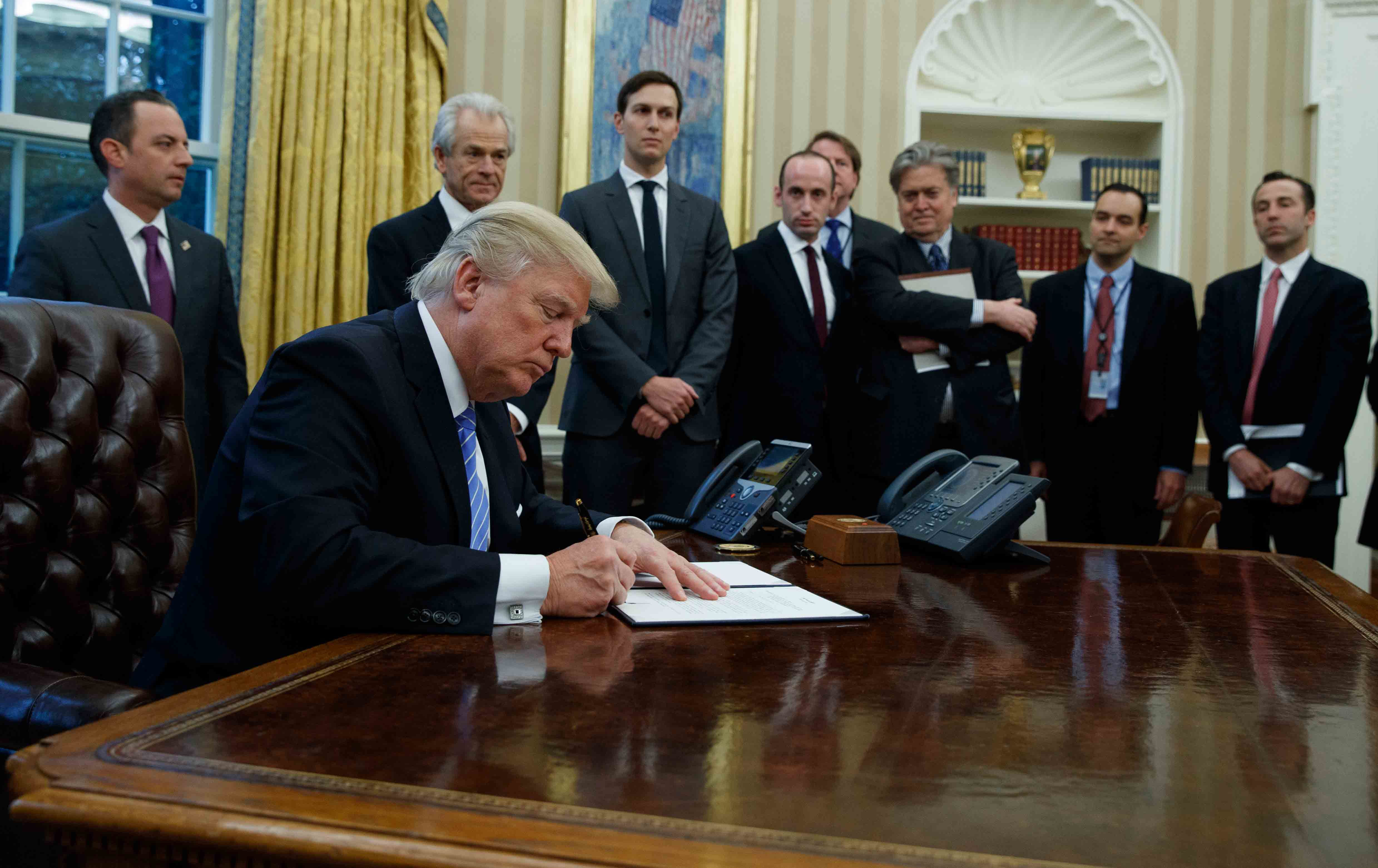 Accompanied by a line-up of his white male advisers, President Donald Trump signed a