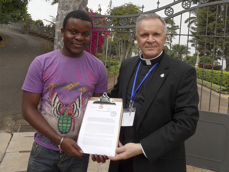The Foundation raised funds for the burial of murdered Cameroonian activist and journalist Eric Lembembe and sponsored activists to speak at the African Commission on Human and People's Rights in 2015, demanding a government inquiry into his death. In this photo, Fr. Ogle and Cameroonian human rights defender Jean Pierre prepare to give local Catholic authorities a copy of a letter to the Vatican condemning an anti-gay hate message from the Catholic Archbishop of Cameroon. He was later removed from office for corruption by the Pope. (Photo courtesy of Albert Ogle)