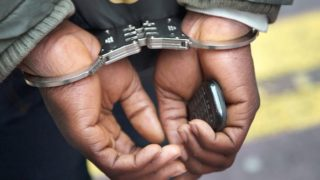 File photo of the hands of a man under arrest.