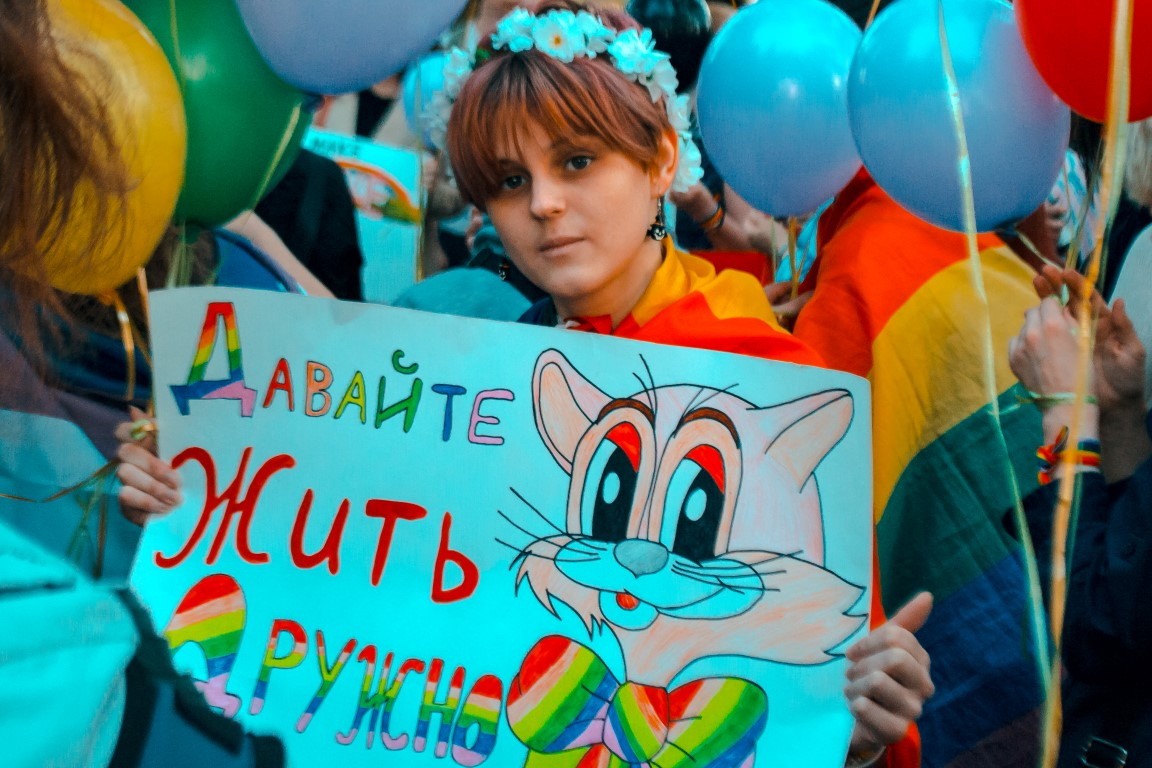 """Young participant at Coming Out's rally for LGBT* rights holds a sign that states """"Let's Live in Peace."""" (Photo courtesy of Coming Out)"""