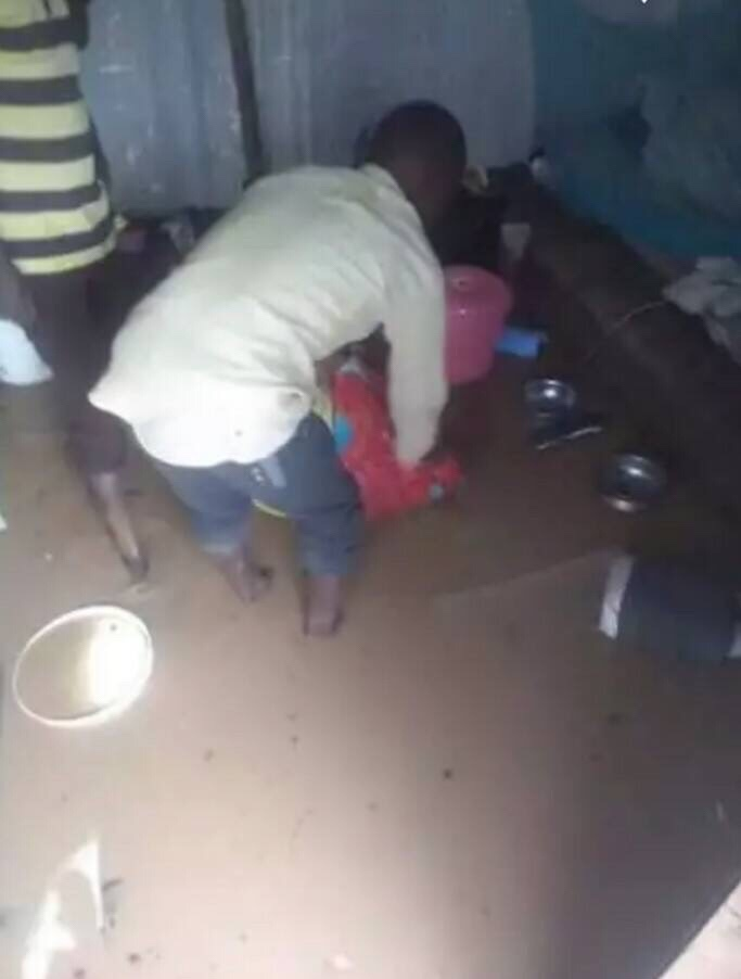 LGBTI refugee in Kakuma Camp wades into his flooded shelter to retrieve household items. (Photo courtesy of Moses Mbazira)