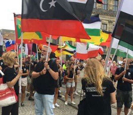 """Marchers wearing black T-shirts with """"Erasing 76 Crimes"""" on the back carry the flags of nations of anti-gay laws. (Photo courtesy of Pride Walk)"""