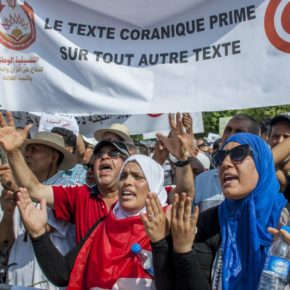 """Protesters carry a banner reading """"Quran text before any other text"""" outside the Tunisian capital of Tunis on Aug. 11. (Hassene Dridi photo courtesy of the Associated Press)"""