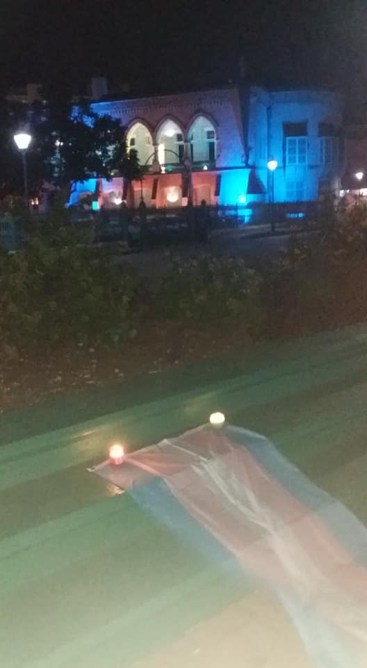 During the ceremony of Trans remembrance, the Trans Pride flag was displayed in front of Barbados' House of Assembly, uplit in the country's blue and yellow national colours to celebrate the country's independence. The flag was anchored by four candles, each one representing 100 Trans and Gender Non-conforming persons who were lost to transphobia and gender based violence between 2017 and 2018. (Photo courtesy of Alexa Hoffman)
