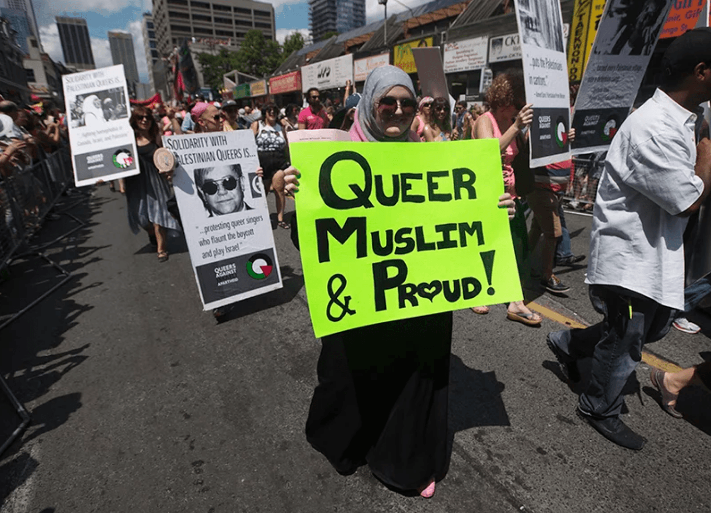 "A woman marching in the Tornonto Pride Parade in 2012 carries a sign that reads, ""Queer, Muslim and Proud."" (Mark Blinch photo courtesy of Religion News/Reuters)"