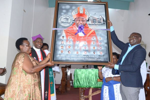 The outgoing Archbishop of the Church of Uganda, the Most Rev, Stanley Ntagali (2nd left), receives a caricature from James Abola (right), the head of laity at All Saints Church, Nakasero. (Photo courtesy of the Daily Monitor)