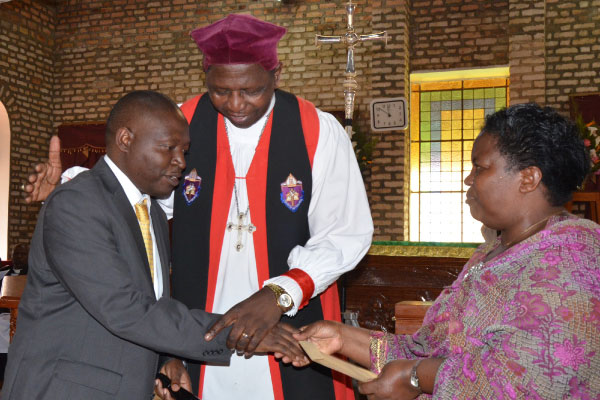 David Bahati (left) congratulates outgoing Bishop Ntagali (centre) and wife on their anti-gay stance during a service in August 2019.