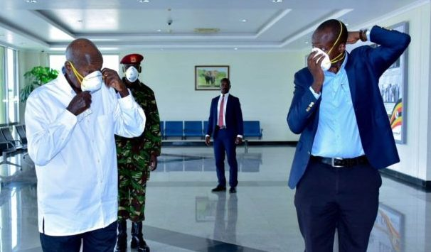 Ugandan President Yoweri Museveni (left) tries on a face mask to protect him against Covid-19.