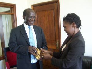 Uganda's current vice president, Edward Ssekandi (left), receives satchets of condoms and water-based sex lubricants from sex worker rights activist Macklean Kyomya while he was still speaker of Uganda Parliament during a petition on non-discrimination to HIV services by sex workers and homosexuals in Kampala. (UhspaUganda photo)
