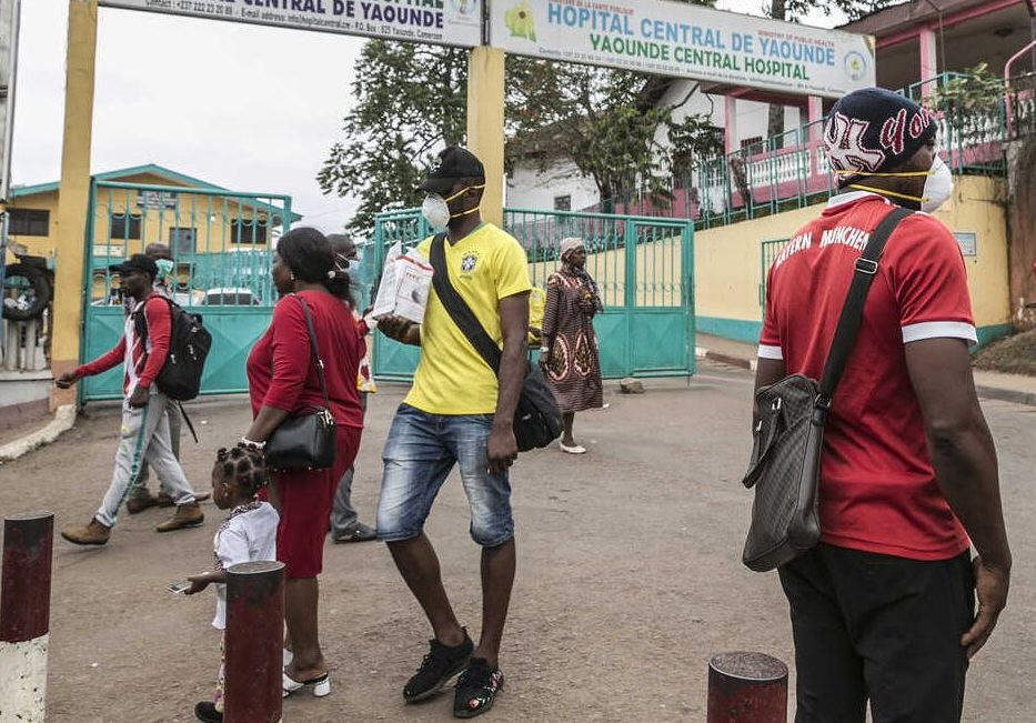 Passersby wearing masks walk by the entrance to the Yaounde General Hospital in Cameroon on March 6 -- before a more extensive lockdown was imposed. (Photo courtesy of VOA and AFP)