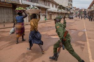 To enforce the countrywide Covid-19 lockdown, a member of Uganda's security forces beats women selling fruit in Kampala on March 26. (Photo courtesy of The East African)