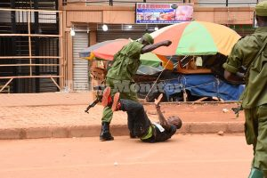 A member of Uganda's security forces beats a man in Kampala to enforce a Covid-19 lockdown issued by Ugandan President Yoweri Museveni. (Photo couresy of the Daily Monitor)