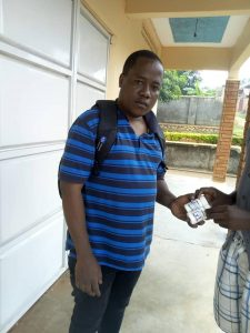 Joseph Kaweesi, the executive director of the community organisation Come Out Post Test Club (COPTEC) delivers ARTs to an LGBT community member. (COPTEC Uganda photo)
