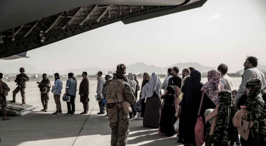 Evacuees wait to board a Boeing C-17 Globemaster III during an evacuation at Hamid Karzai International Airport in Kabul, Afghanistan, on Aug., 2021. U.S. Marine Corps/Staff Sgt. Victor Mancillal photo handout courtesy of Reuters.